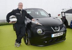 Chubby bloke poses next to pricey Nissan